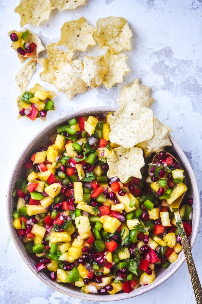 pomegranate pineapple salsa hero shot in bowl with chips and spoon