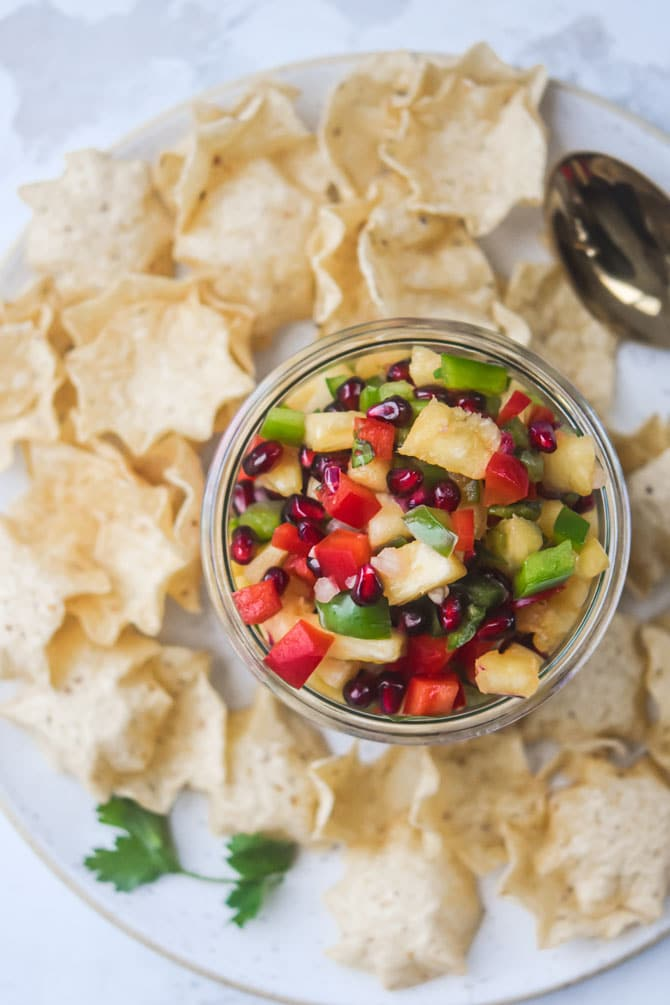 pomegranate pineapple salsa flat lay with salsa in weck jar with spoon chips surrounding