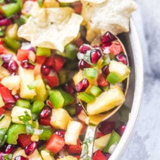 pomegranate pineapple salsa presented on a gold spoon
