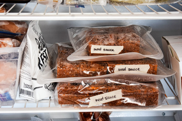 meat sauce in silicone bags laying flat in freezer and labelled