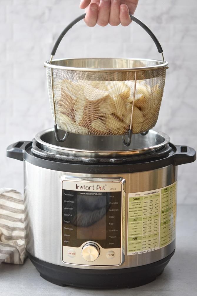 Diced potatoes in Instant pot basket held up