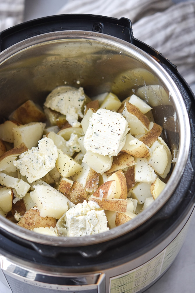 Diced potatoes in instant pot with boursin cheese