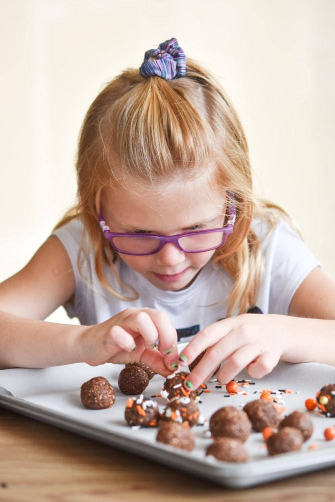 Healthy Halloween Brownie Bites kid helping decorate