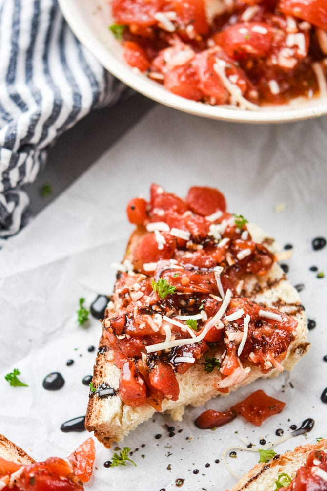 close up bruschetta on bread with bowl in background