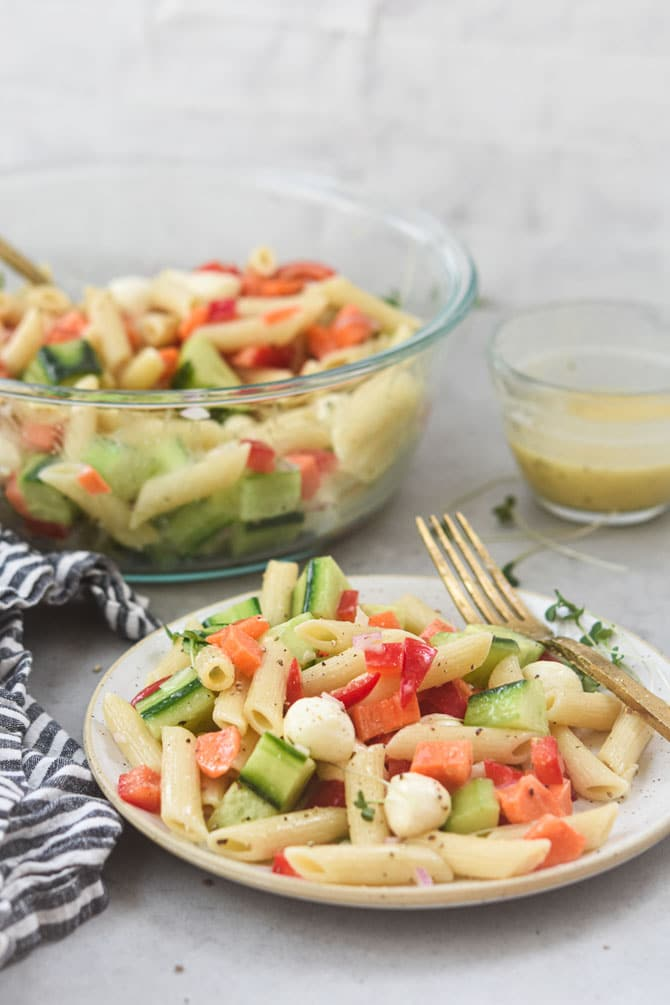 pasta salad plated straight on with bowl in the background