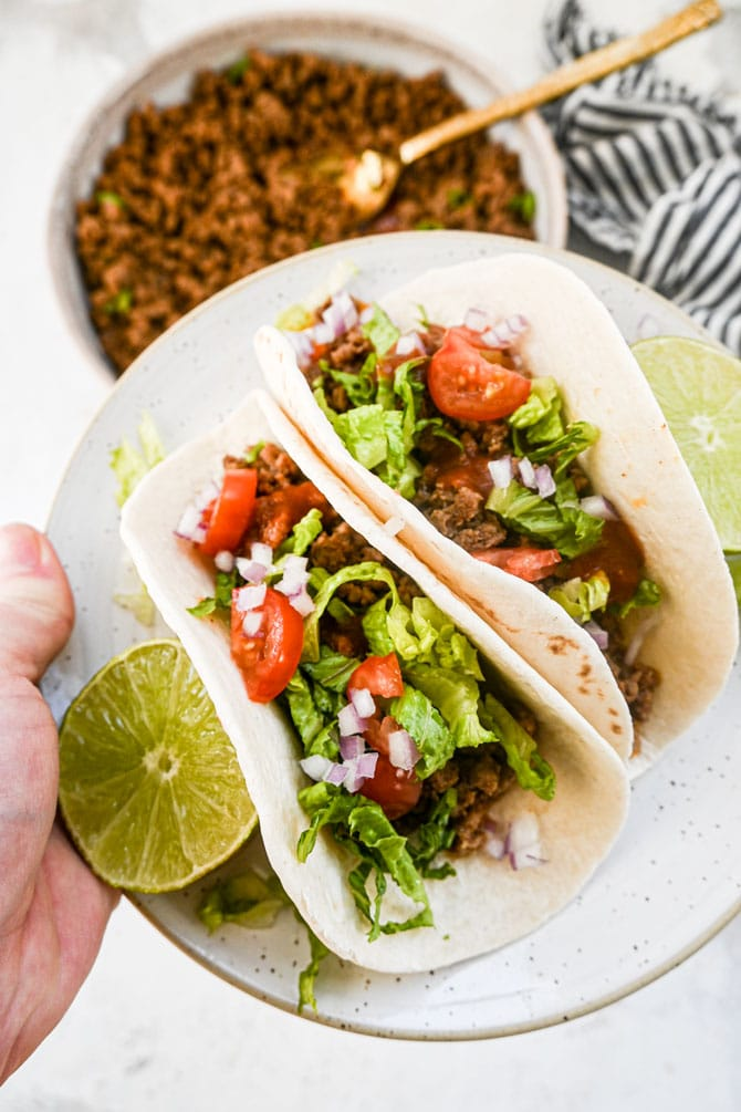 ground beef tacos on a plate being held