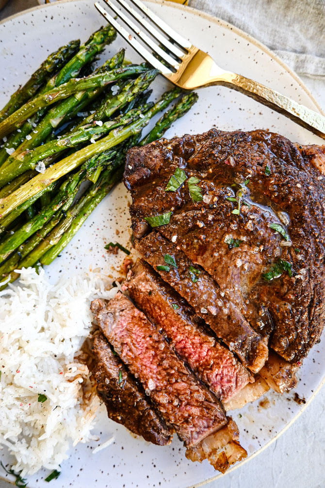 Air fryer steak sliced on a plate with rice and asparagus